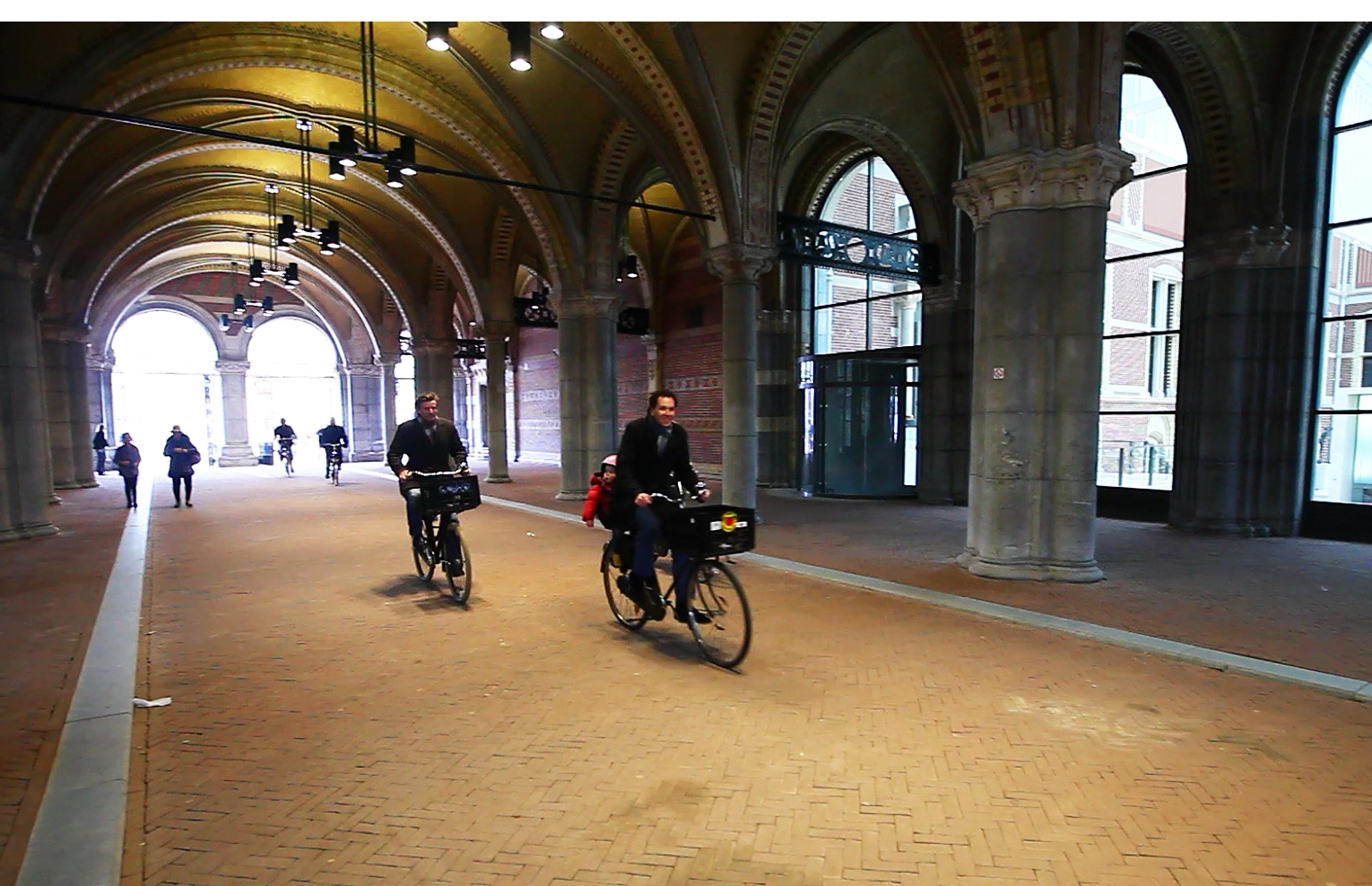 Red Amsterdam-raadslid Roderic Evans-Knaup en Groene Amsterdammer-directeur Teun Gautier fietsen onder het Rijksmuseum door